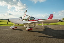 Single turboprop aircraft on the ground in sunny day, cirrus