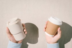 Single-Use Plastic Bans The Environment Problem issue with Disposable Coffee Cups. Top view hands of a man holding reusable cup and disposable cup with plastic lid. Environmental milestone, Zerowaste.