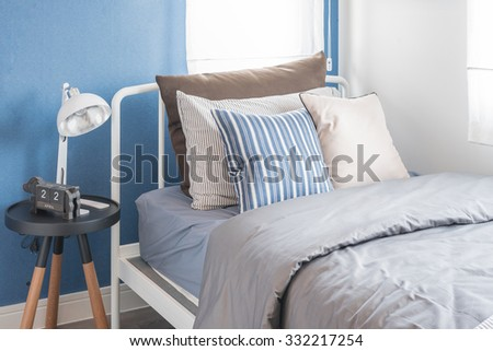 single white bed with white lamp and blue wall in kid's bedroom