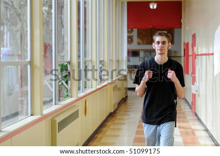 Single white Caucasian male young adult walks through his school hallway with his hands on his backpack straps.