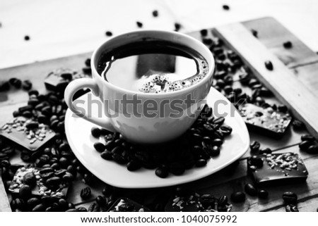 Single white cup on a wood or wooden table filled with black coffee beans and almond chocolate bars black and white photography