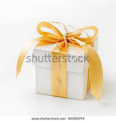 Single white gift box with gold ribbon on white background.