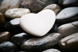 Single white heart on black pebble stones,  still life.