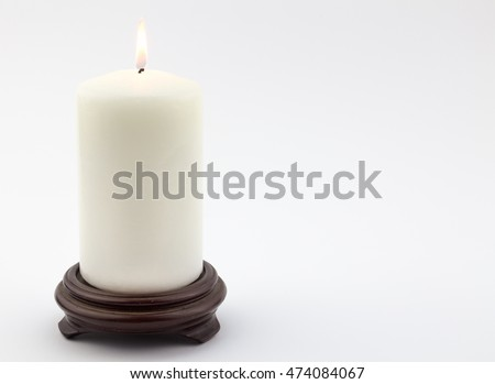 Single white lit candle on wood stand isolated on white background