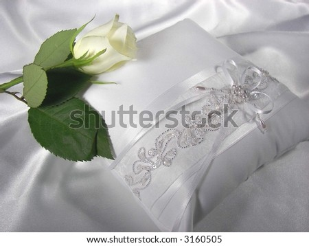 Single white rose on a elegant white wedding pillow with bow and sequins