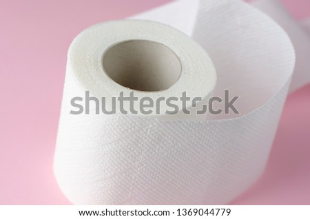 Single white toilet paper roll on pastel pink background. Space for text. Everyday use object. Hygienic object