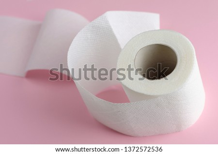 Single white toilet paper roll on pastel pink background. Space for text. Everyday use object. Hygienic object #1372572536
