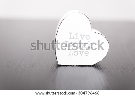 Single white wooden heart with the slogan live laugh love on the front
