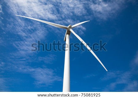 single wind turbine low angle against blue sky with clouds