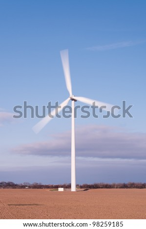 Single wind turbine vertical showing motion blur of the moving blades - stock photo