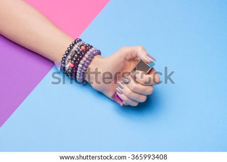 Single woman hand, wearing jewelry, in various background colors. Graphic look, solid bold colors, close up shot. #365993408