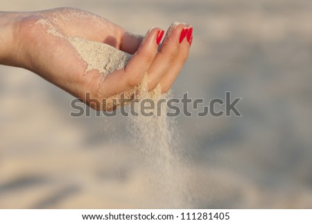 Single woman hand with sand and red nails
