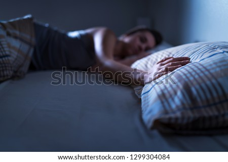 Single woman sleeping alone in bed at home. Lonely lady missing husband or boyfriend. Hand on pillow. Solitude, infidelity or heartbreak concept. Loneliness and sorrow after break up or divorce. #1299304084