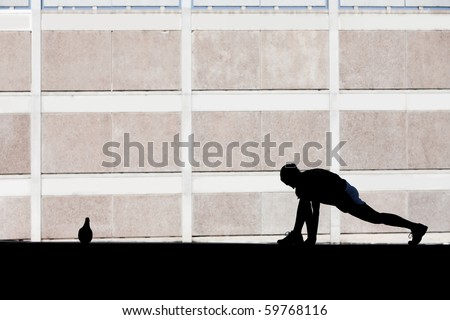 Single woman stretches before she goes for run.