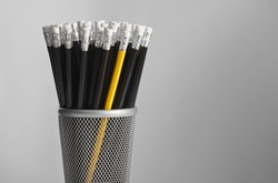 Single yellow pencil in pot of black pencils.