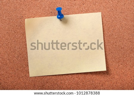 Single yellow sticky post note pinned pushpin cork board