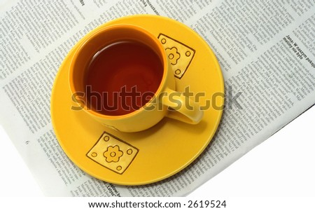 Single yellow tea cup on a newspaper