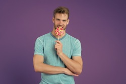 Singles Day. Happy eating sweets. Symbol of happiness. Man eat lollipop. Man smiling hold lollipop. Holiday concept. Unofficial holiday for bachelors. Guy lollipop candy violet background. Sweet boy.