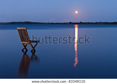 Singular chair in calm water facing the land in the horizon. With rising orange moon reflected in the blue water