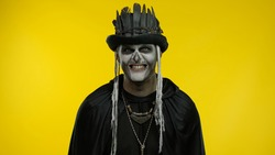 Sinister man with horrible Halloween skeleton makeup in costume with top-hat making faces, looking at camera trying to scare. Horror theme. Day of The Dead. Yellow background. Copy space