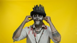 Sinister man with horrible Halloween skeleton makeup with top-hat puts on headphones and starts dancing, celebrating. Horror theme. Day of The Dead. Isolated on yellow background