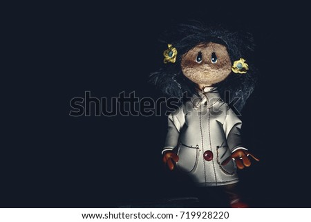 Sinister rag doll with white leather trench coat, in darkness. Original photo of ancient toy (copyright free) retouched and colored, neither artworks, layers nor external references were used