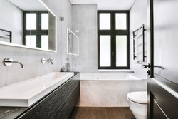 Sink and mirror located near flush toilet and bathtub against concrete wall with window
