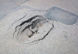Sinkhole in the asphalt  road. The need to repair the roadway.