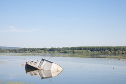 Sinking boat, an abaondoned passenger ship, rusting in the waters of the Danube river in Serbia, during summer, in a natural park. Danube is one of the biggest rivers of Europe.