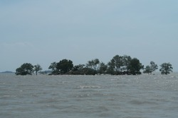 Sinking island by the tide in the middle of indonesian sea