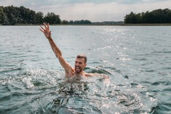 Sinking person calls for help. Hand drowning man sticking out of the water.