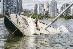 Sinking sailboat abandonned on the shore of a city