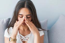 Sinus ache causing very paintful headache. Unhealthy woman in pain. Sharp strong sore. Sinus pain, sinus pressure, sinusitis. Sad woman holding her nose and head because sinus pain