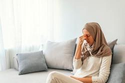 Sinus pain, sinus pressure, sinusitis. Sad Muslim woman holding her nose and head because sinus pain. Sinus ache causing very paintful headache. Unhealthy woman in pain. Sharp strong sore