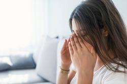 Sinus pain, sinus pressure, sinusitis. Sad woman holding her nose and head because sinus pain. Sinus ache causing very paintful headache.
