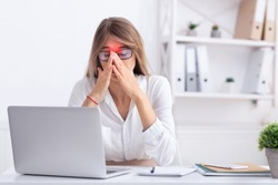 Sinusitis. Sad Businesswoman Suffering From Sinus Pain Touching Red Zone On Nosebridge Sitting At Workplace. Copy Space