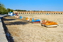 SioSe Pol bridge over the Zayandeh River in Isfahan city in Iran, the name of the bridge is by thirty-three arches on the bridge. A dry riverbed with colorful water pedal boats in the shape of a swan.