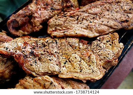 Sirloin or sirloin, piece of beef from the back of the beef on a grilled on charcoal. Beef steak sirloin on fire. The meat is sprinkled with ground black pepper and coarse sea salt