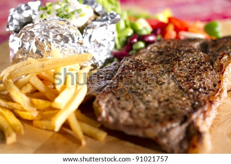 sirloin steak meal, sirloin steak meal on dish with fries baked potato and salad.