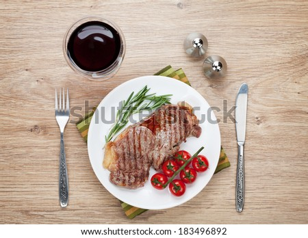 Sirloin steak with rosemary and cherry tomatoes on a plate with wine. View from above
