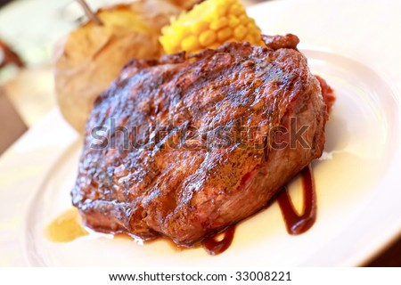 sirloin strip steak with corn cob ,vegetables and savory sauce