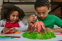 Sister and brother having fun making DIY volcano model from kids play clay for school project. Home education concept.