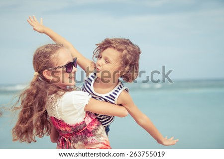 Sister and brother playing on the beach at the day time. Concept Brother And Sister Together Forever