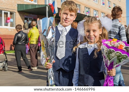 Sister and brother with the flowers on the first day of school
