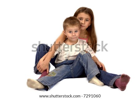 Sister and little brother sitting on the floor together isolated on white