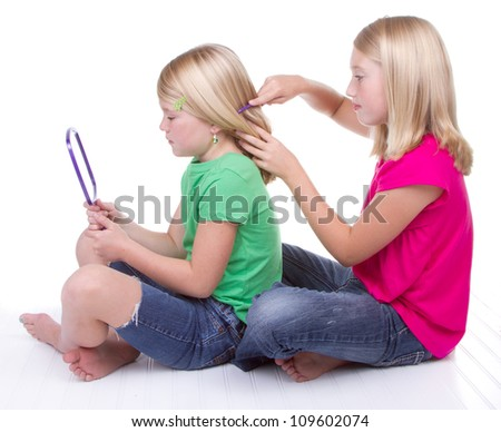 sister combing younger sisters hair, white background