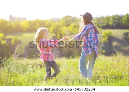 Sister girls having fun in the meadow