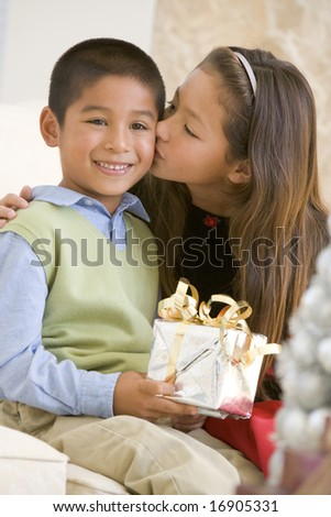 Sister Giving Her Brother A Christmas Present And Kissing Him On The Cheek