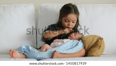 Sister holding newborn baby infant kissing showing love and affection