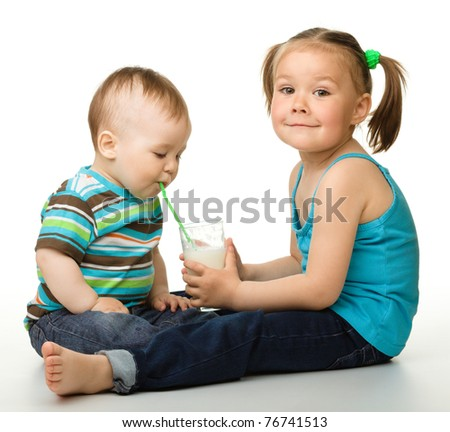 Sister is feeding her little brother and he drinks milk using drinking straw, isolated over white